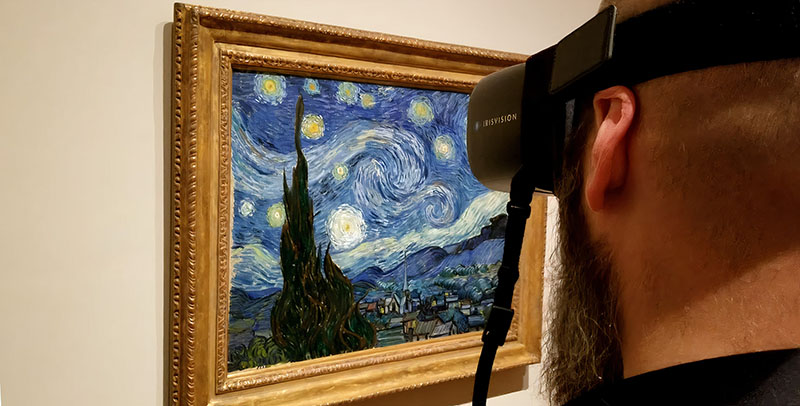 Sam from The Blind Life using wearable low vision glasses by IrisVision to look at The Starry Night painting by Van Gogh at the Museum of Modern Art located in New York.